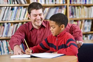 Tutor Helping Male Pupil With Reading At Desk